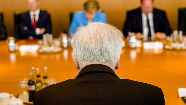 German Interior Minister Horst Seehofer, front, sits on the opposite of German German Chancellor Angela Merkel, center back ground, prior to the weekly cabinet meeting of the German government at the chancellery in Berlin, Wednesday, June 13, 2018. - Sputnik International