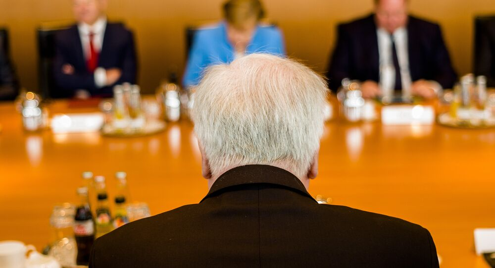 German Interior Minister Horst Seehofer, front, sits on the opposite of German German Chancellor Angela Merkel, center back ground, prior to the weekly cabinet meeting of the German government at the chancellery in Berlin, Wednesday, June 13, 2018.