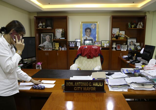 A staff member of Tanauan city Mayor Antonio Halili arranges items inside his office after he was killed earlier in Batangas province, south of Manila on Monday, July 2, 2018