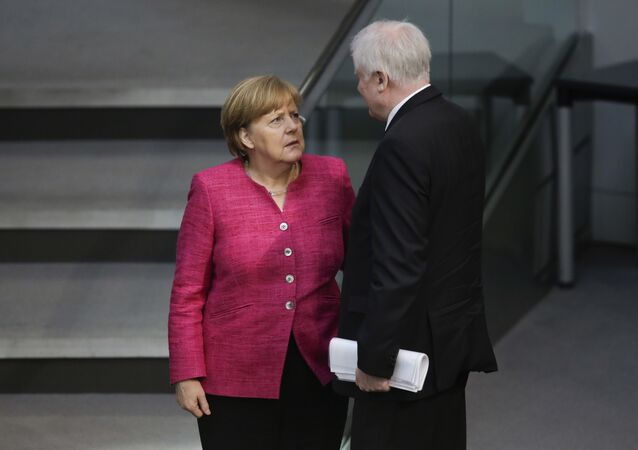 In this May 15, 2018 file photo German Chancellor Angela Merkel, left, talks with German Interior Minister Horst Seehofer, right, during the first day of the budget 2018 debate at the parliament Bundestag at the Reichstag building in Berlin