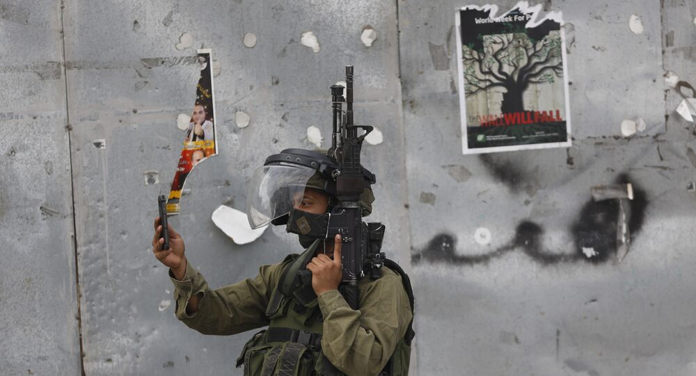 An Israeli soldier takes a photograph with his mobile phone during clashes with Palestinian demonstrators in the West Bank city of Bethlehem on Tuesday, Oct. 13, 2015. A pair of Palestinian men boarded a bus in Jerusalem and began shooting and stabbing passengers, while another assailant rammed a car into a bus station before stabbing bystanders, in near-simultaneous attacks Tuesday that escalated a monthlong wave of violence