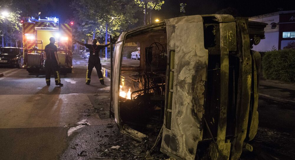 Firefighters work near a burnt car in the Breil neighborhood of Nantes early on July 4, 2018. Groups of young people clashed with police in the western French city of Nantes on the night of July 3 after a man was shot dead by an officer during a police check