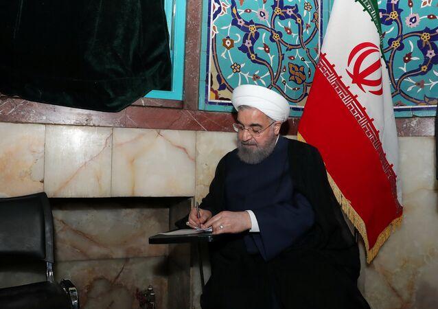 Iran's President Hassan Rouhani fills in his ballot