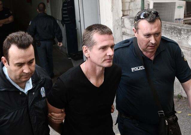 Russian Alexander Vinnik (C) is escorted by police officers as he arrives at a courthouse in Thessaloniki on October 4, 2017. Alexander Vinnik, who headed BTC-e, an exchange he operated for the Bitcoin crypto-currency, was indicted by a US court in late July on 21 charges ranging from identity theft and facilitating drug trafficking to money laundering