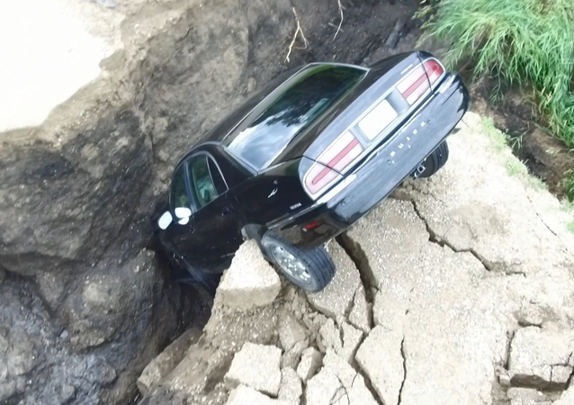 Screenshot From Drone Footage of a Minnesota Driver's Car that Plunged into a Hole Created by Rain, July 3, 2018