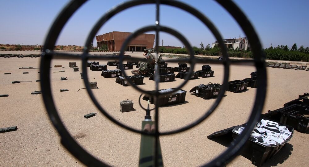 Syrian government forces' soldiers display weapons confiscated from the rebels in a Syrian army military base in the town of Ezraa, province of Daraa, on July 4, 2018