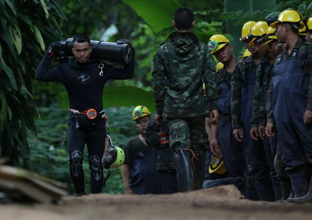 A diver carries an oxygen tank as he leaves the Tham Luang cave complex, where 12 boys and their soccer coach are trapped, in the northern province of Chiang Rai, Thailand, July 6, 2018