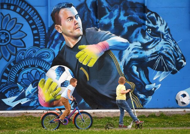 Children are looking at graffiti depicting Igor Akinfeev, the goalkeeper of the Russian national football team, in Shchyolkovo, Moscow region