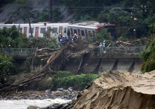 An emergency crew works at the site after a train derailed due to landslides caused by heavy rain in Karatsu city, Saga prefecture on July 7, 2018