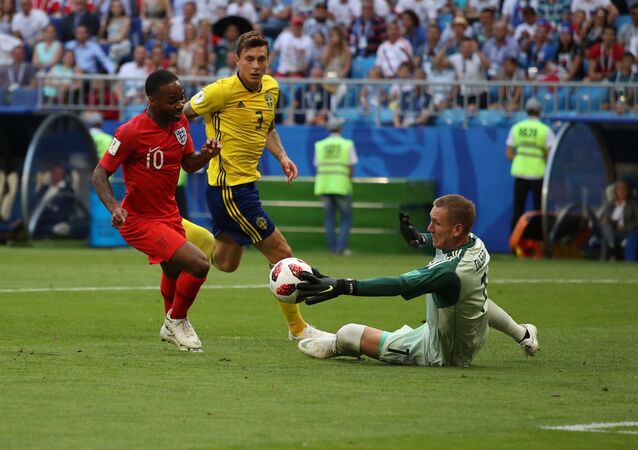 Sweden's goalkeeper Robin Olsen, right, makes a save against England's Raheem Sterling during the World Cup quarterfinal soccer match between Sweden and England at the Samara Arena, in Samara, Russia, July 7, 2018
