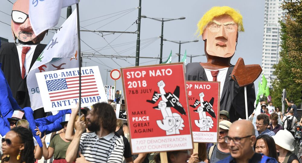 Protestors march next to giant puppets of U.S. President Donald Trump, right, and Belgian Prime Minister Charles Michel, left, during a demonstration in Brussels, Saturday, July 7, 2018