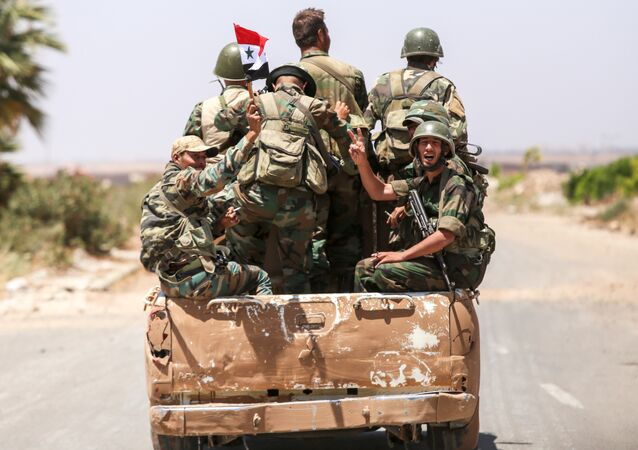A Syrian government soldier flashes the victory gesture while riding in the back of a pickup truck with comrades at the Nassib border crossing with Jordan in the southern province of Daraa on July 7, 2018