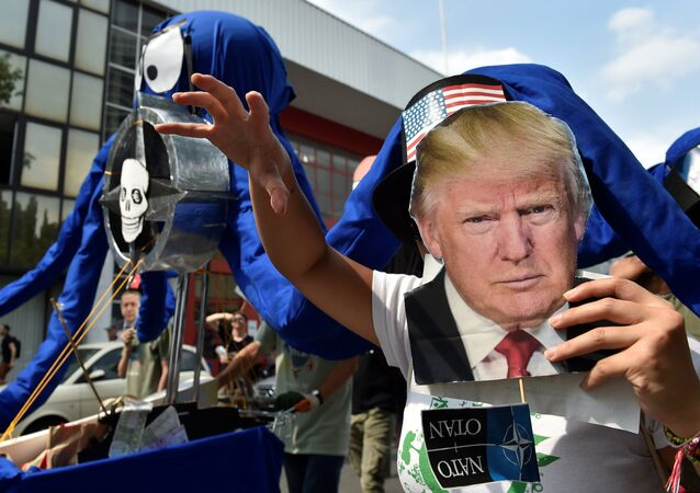 A participant holds the portrait of U.S. President Donald Trump as protesters take part in a march against the NATO leaders summit, in Brussels, Belgium July 7, 2018.