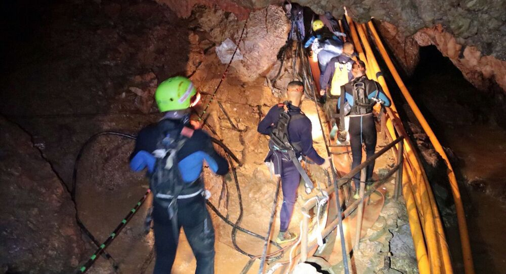 In this undated photo released by Royal Thai Navy on Saturday, July 7, 2018, Thai rescue team members walk inside a cave where 12 boys and their soccer coach have been trapped since June 23, in Mae Sai, Chiang Rai province, northern Thailand