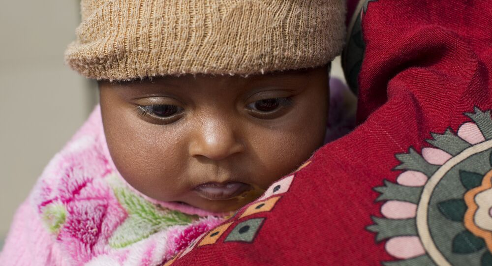 A mother waits with her infant to be seen by a doctor at a children ward of Poly Clinic in Islamabad, Pakistan