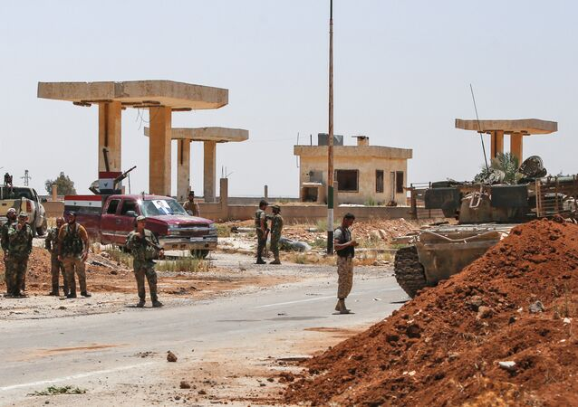 Syrian government soldiers stand by a tank and armed pickup trucks at the Nassib border crossing with Jordan in the southern province of Daraa on July 7, 2018