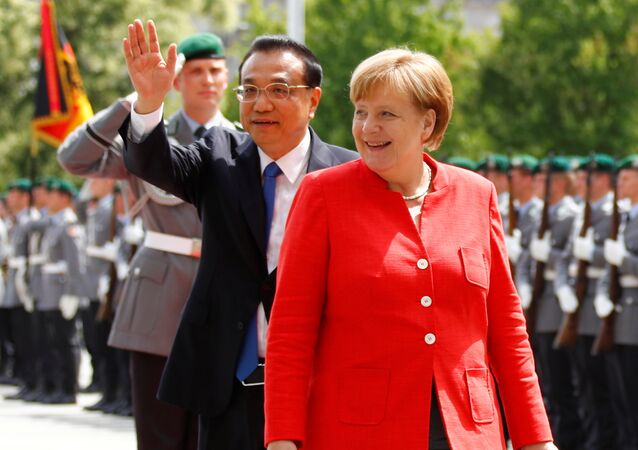 German Chancellor Angela Merkel and Chinese Prime Minister Li Keqiang review the guard of honour at the chancellery in Berlin, Germany, July 9, 2018