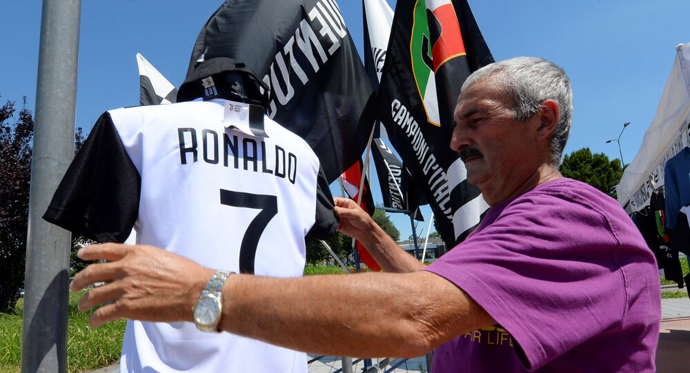 A vendor adjusts a Juventus' jerseys with the name of Cristiano Ronaldo exhibited in his shop in Turin, Italy July 7, 2018