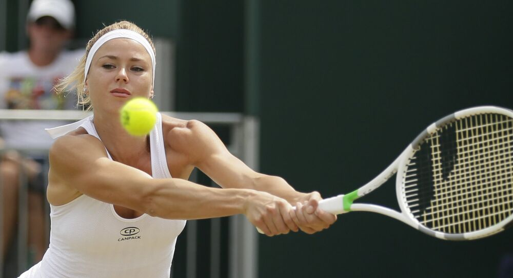 Italy's Camila Giorgi returns the ball to Russia's Ekaterina Makarova during their women's singles match, on day seven of the Wimbledon Tennis Championships, in London, Monday July 9, 2018