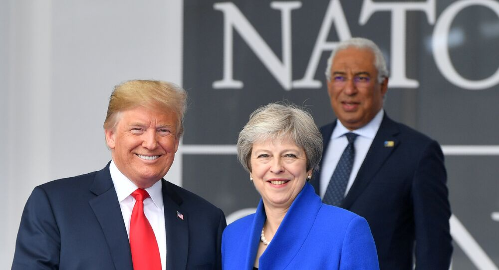 US President Donald Trump (L) gestures as he poses alongside Britain's Prime Minister Theresa May (R) as Portugal's Prime Minister Antonio Costa (TOP) looks on during the opening ceremony of the NATO (North Atlantic Treaty Organization) summit, at the NATO headquarters in Brussels, on July 11, 2018.