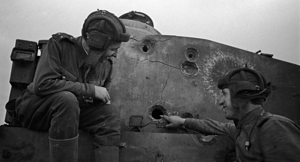 Two Soviet tankmen sitting on a disabled Tiger tank. The Kursk Bulge