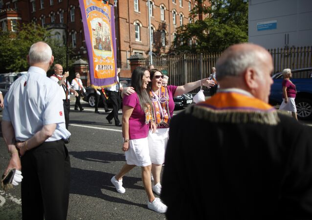 Protestant women pose for a selfie during an Orange Order march in Belfast on July 12, 2017