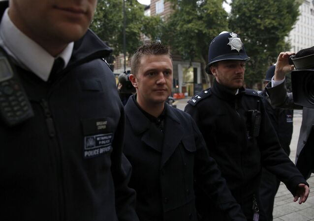 Tommy Robinson, the former leader of the right-wing EDL English Defense League group, is flanked by police officers as he arrives for an appearance at Westminster Magistrates Court in London, Oct. 16, 2013
