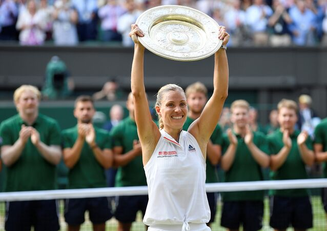 Tennis - Wimbledon - All England Lawn Tennis and Croquet Club, London, Britain - July 14, 2018 Germany's Angelique Kerber holds the trophy after winning the women's singles final against Serena Williams of the U.S.