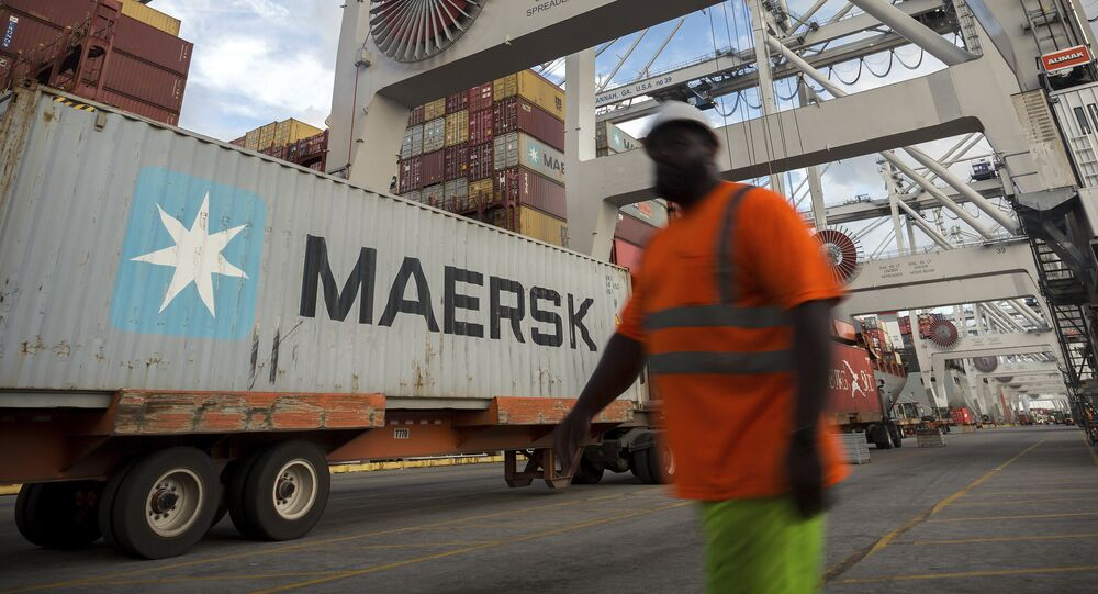 In this Thursday, July, 5, 2018 photo, a longshoreman prepares to direct the next shipping container to be picked up by a ship to shore crane at the Port of Savannah in Savannah, Ga.