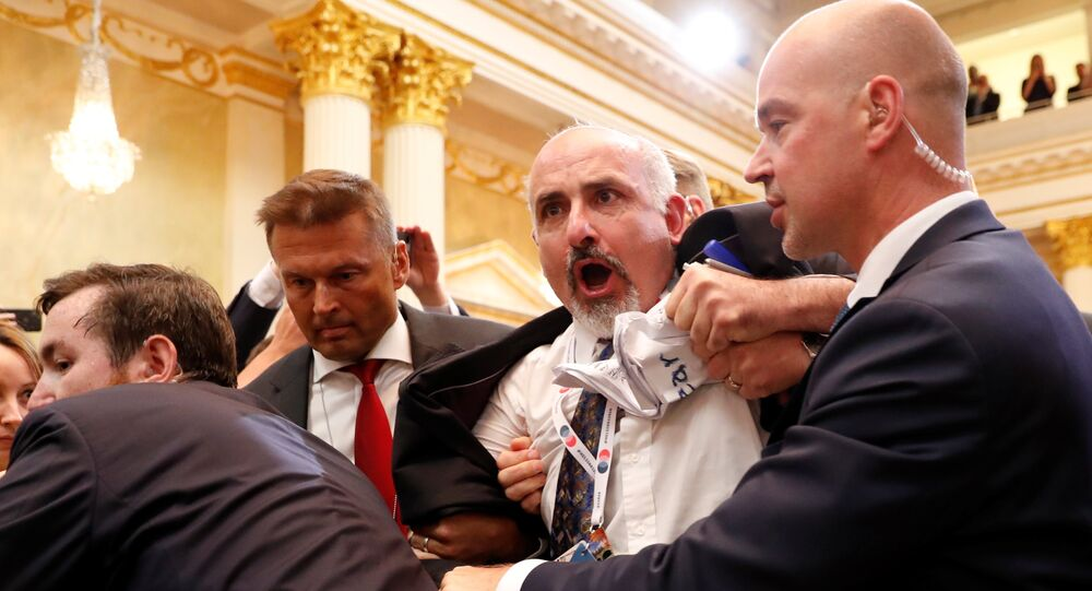 Security personnel removes a man from the premises before U.S. President Donald Trump and Russia's President Vladimir Putin hold a joint news conference, after their meeting in Helsinki, Finland, July 16, 2018