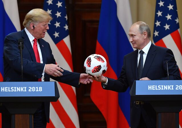 Russia's President Vladimir Putin (R) offers a ball of the 2018 football World Cup to US President Donald Trump during a joint press conference after a meeting at the Presidential Palace in Helsinki, on July 16, 2018