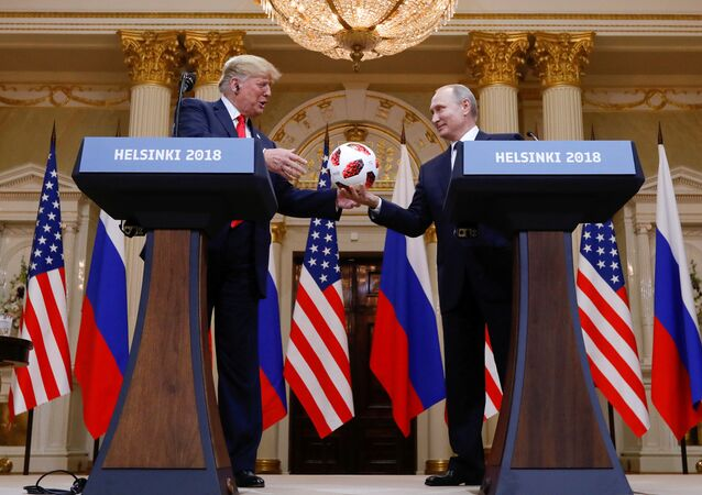 U.S. President Donald Trump receives a football from Russia's President Vladimir Putin during their joint news conference after a meeting in Helsinki, Finland, July 16, 2018