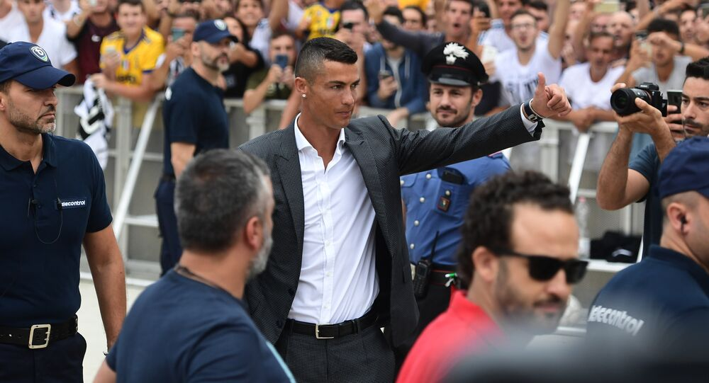 Cristiano Ronaldo waves to suppoters as he arrives on July 16, 2018 at the Juventus medical centre at the Alliance stadium in Turin