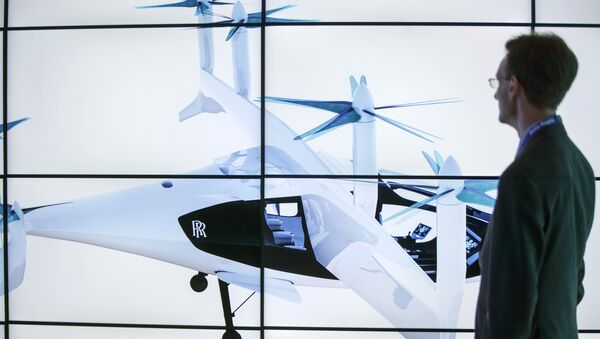A man poses alongside screens presenting the Rolls-Royce EVTOL air taxi concept during the Farnborough Airshow, south west of London, on July 16, 2018 - Sputnik International