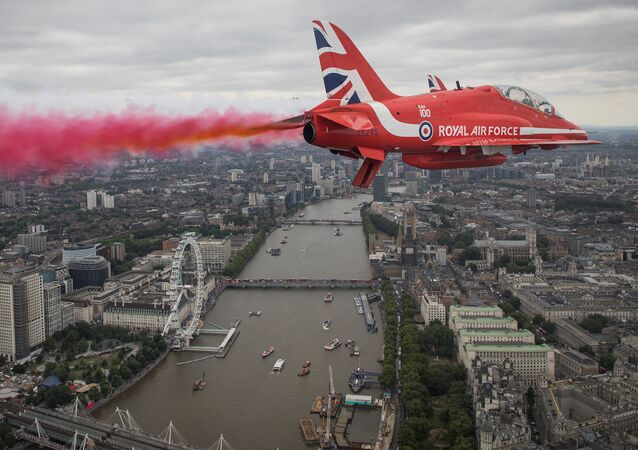 Members of the Red Arrows Royal Air Force Aerobatic Team fly over London, heading for Buckingham Palace, to mark the centenary of the Royal Air Force in central London, Britain.