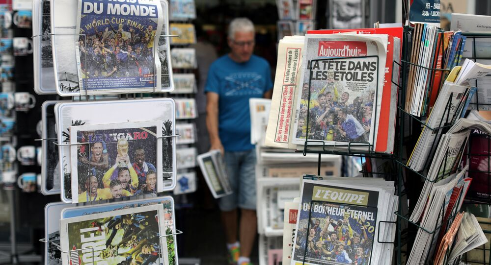 A man walks past racks which display copies of French daily newspapers with front pages about France's win in the World Cup, in Nice, France, July 16, 2018