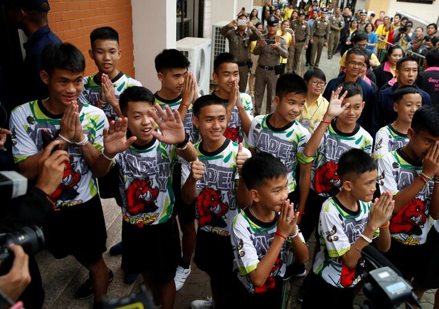 The 12 boys and their soccer coach who were rescued from a flooded cave arrive for a news conference in the northern province of Chiang Rai, Thailand, July 18, 2018