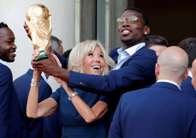 Brigitte Macron, the wife of French President Emmanuel Macron (not pictured), and player Paul Pogba hold the trophy before a reception to honour the France soccer team after their victory in the 2018 Russia Soccer World Cup, at the Elysee Palace in Paris, France, July 16, 2018
