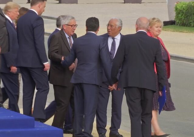 In this Wednesday, July 11, 2018 grab taken from video, European Union leader Jean-Claude Juncker, centre left is helped by Heads of States, at Brussels Parc Cinquantenaire, in Brussels, Belgium