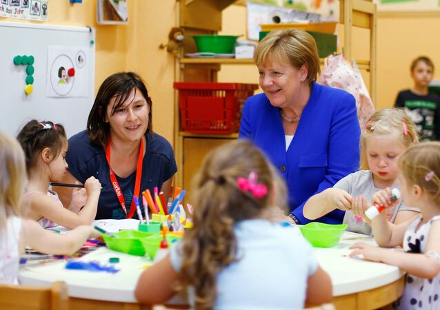 Chancellor Angela Merkel sits with kids at the Caritas Association kindergarten in Cologne, Germany, July 18, 2018