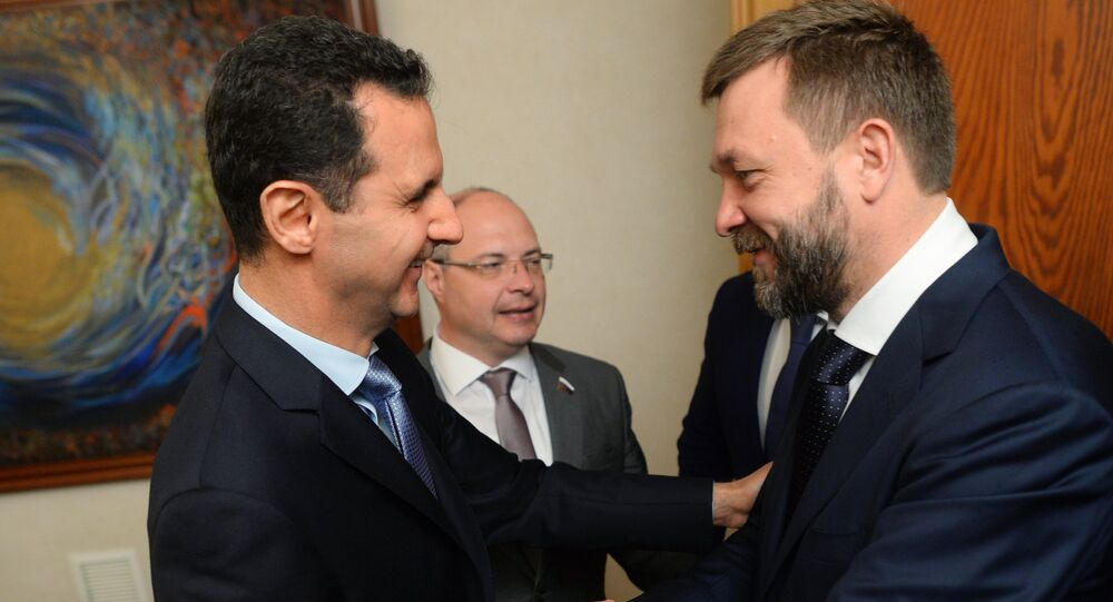 Syrian President Bashar al-Assad, left, meets with the Russian Federation Council Dmitry Sablin  in Damascus
