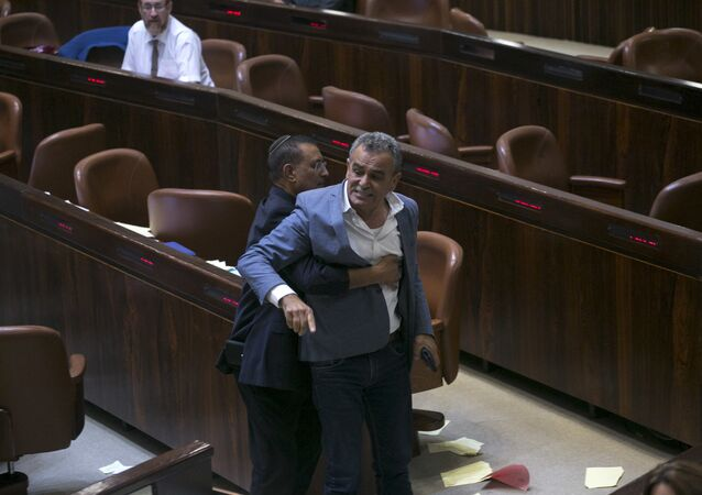 A Knesset usher removes Jamal Zahalka, an Israeli Arab member of the Knesset representing the Balad party, who was protesting the passage of a contentious bill, during a Knesset session in Jerusalem, Thursday, July 19, 2018. Israel's parliament approved a controversial piece of legislation early Thursday that defines the country as the nation-state of the Jewish people. Opponents and rights groups have criticized the legislation, warning that it will sideline minorities such as the country's Arabs