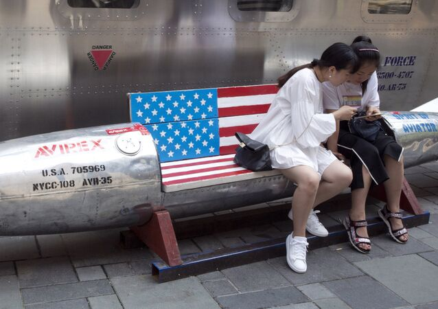 Chinese women look at phone near a rocket shaped bench with an American flag used as a marketing gimmick for a U.S. apparel shop in Beijing, China, Friday, July 6, 2018