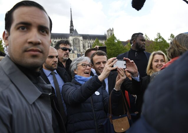 French presidential election candidate for the En Marche ! movement Emmanuel Macron (C-R) poses for a 'selfie' with a supporter outside the Amiens Cathedral on April 26, 2017, as Macron's bodyguard nicknamed Makao (2ndR) and bodyguard Alexandre Benalla (L) stand guard around him