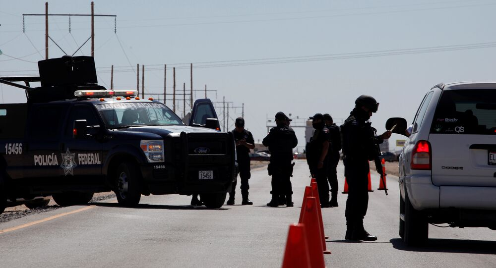 A federal police officer (R) inspect a vehicle at a security checkpoint near a prison in Ciudad Juarez where Mexican drug boss Joaquin Chapo Guzman has been moved from his jail in central Mexico May 7, 2016