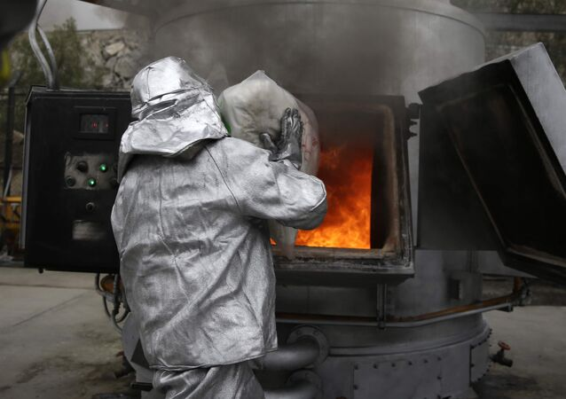 A police officer places a bag of seized cocaine into an incinerator (File)