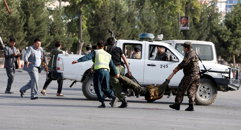 Afghan policemen carry a wounded man at the site of a blast in Kabul, Afghanistan, July 22, 2018