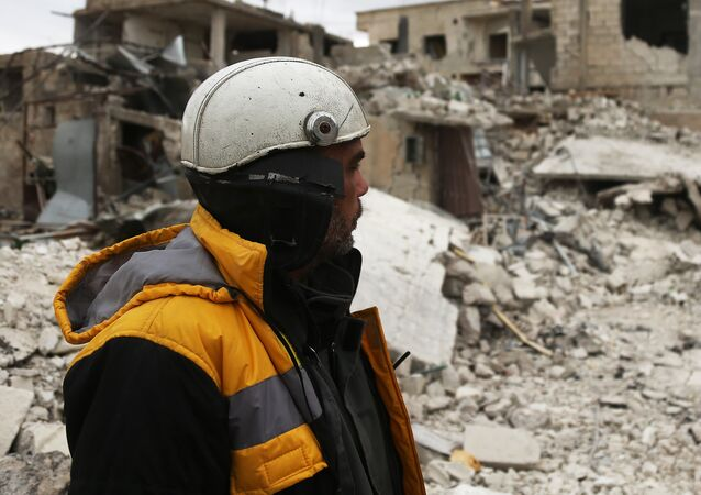 Forty-five-year-old Samir Salim (L) who along with his three brothers are members of the White Helmets rescue forces looks out at destroyed buildings in the town of Medeira in Syria's rebel-held Eastern Ghouta area on February 12 2018.