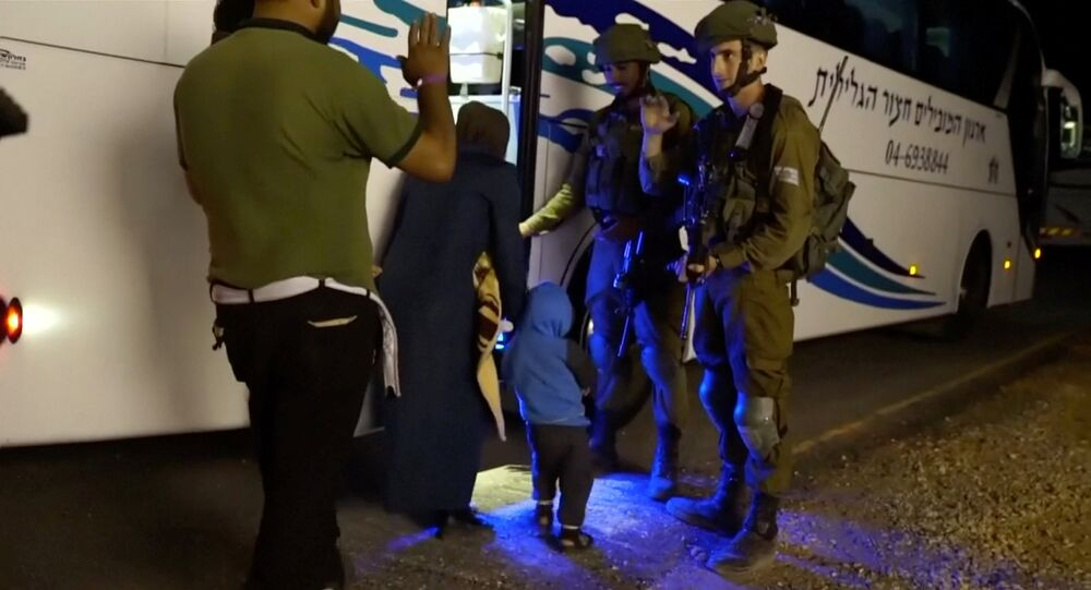 People walk past Israeli soldiers as they board a bus during the Syria Civil Defence, also known as the White Helmets, extraction from the Golan Heights, Israel in this still image taken from video, provided by the Israeli Army July 22, 2018