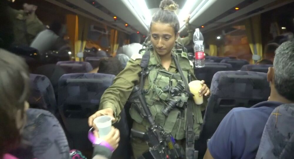 An Israeli solider hands out water on a bus, during the Syria Civil Defence, also known as the White Helmets, extraction from the Golan Heights, Israel in this still image taken from video, provided by the Israeli Army July 22, 2018